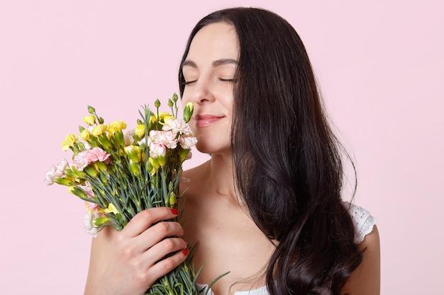 Jovencita de cabello oscuro, vestida con un vestido blanco, tiene una elegante manicura roja, está parada con los ojos cerrados, huele hermosas flores, se ve suavemente, le gusta su ramo, la morena posa sobre rosa