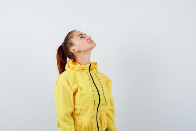 Jovencita de chaqueta amarilla posando mientras mira hacia arriba y parece segura de sí misma, vista frontal.