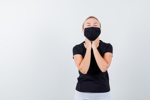 Jovencita cogidos de la mano en la garganta en camiseta, pantalón, máscara médica aislada