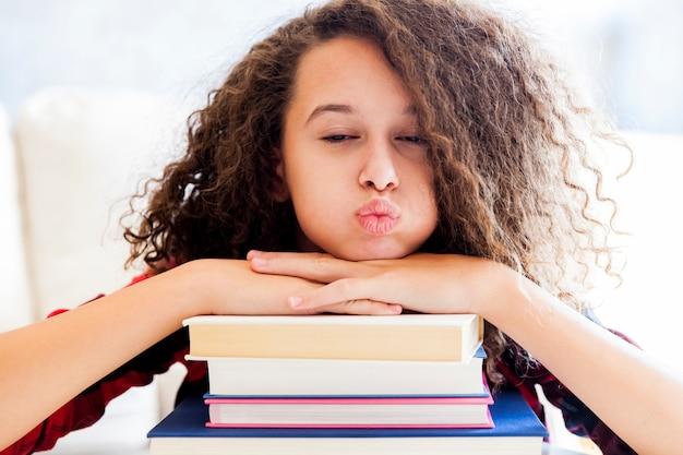 Jovencita descansando sobre libros en la habitación