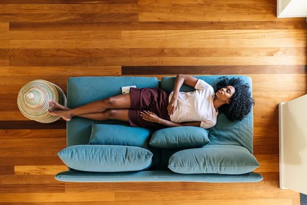 Jovencita durmiendo en el sofá en casa
