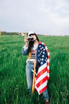 Jovencita en campo con bandera estadounidense