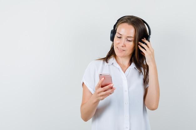 Jovencita escuchando música mientras mira su teléfono en blusa blanca y mira concentrada.