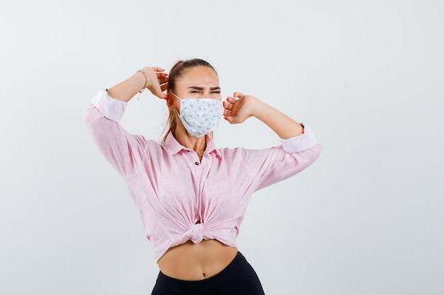Jovencita estirando la parte superior del cuerpo en camisa, máscara y aspecto relajado. vista frontal.