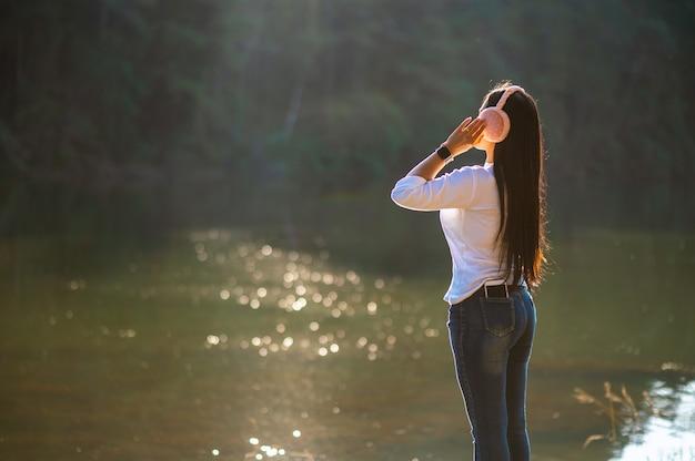 Jovencita está felizmente escuchando música con auriculares en medio de la naturaleza y la cálida luz de la mañana.