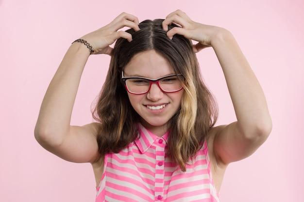 Jovencita con gafas, con el pelo largo rasca su cabeza