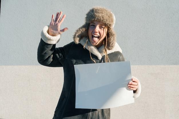 Jovencita graciosa mostrando una hoja de papel blanco limpio