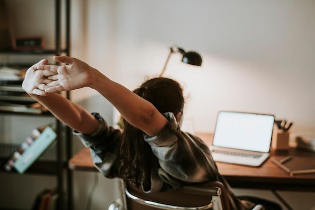 Jovencita haciendo los deberes en su computadora portátil