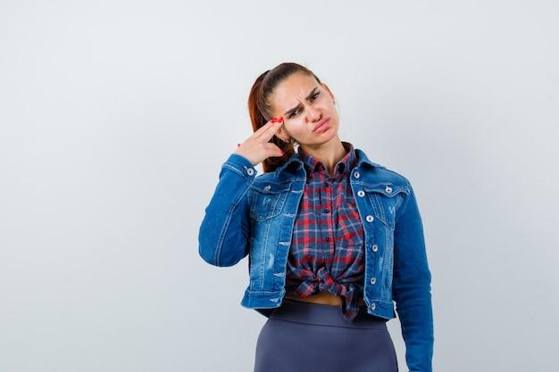 Jovencita haciendo gesto de suicidio en camisa, chaqueta y mirando deprimido, vista frontal.