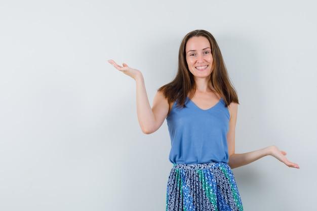 Jovencita haciendo gestos de escalas en camiseta, falda y mirando alegre, vista frontal.