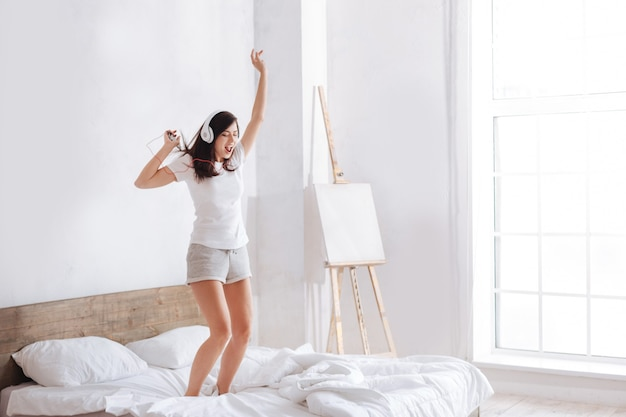 Jovencita juguetona saltando en la cama mientras escucha música con auriculares y un teléfono inteligente en la mano