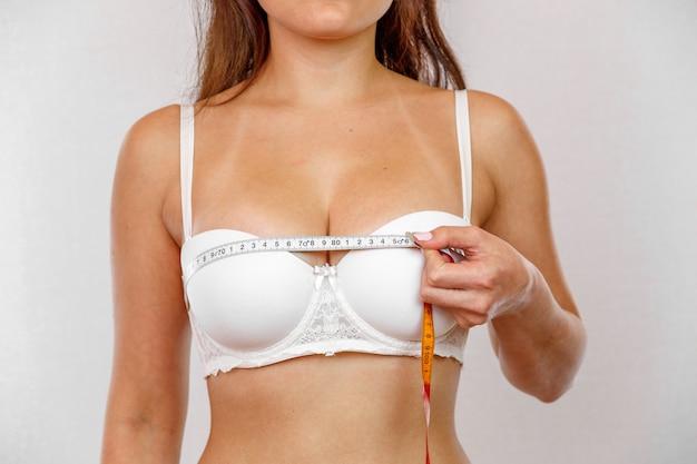 Una jovencita en lencería blanca mide sus senos con un medidor.