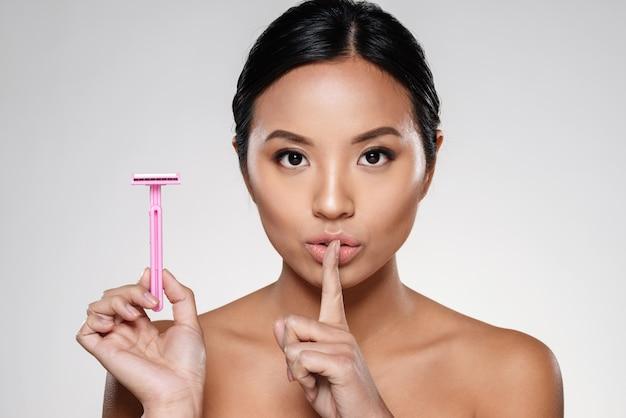 Jovencita con maquinilla de afeitar y mostrando gesto de silencio