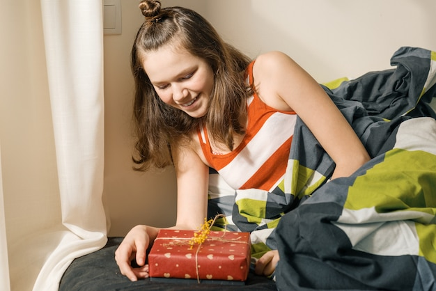 Jovencita mirando y abriendo regalo sorpresa en caja
