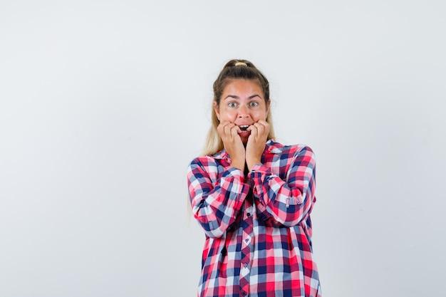 Jovencita mordiéndose las uñas emocionalmente en camisa a cuadros y luciendo agitada. vista frontal.