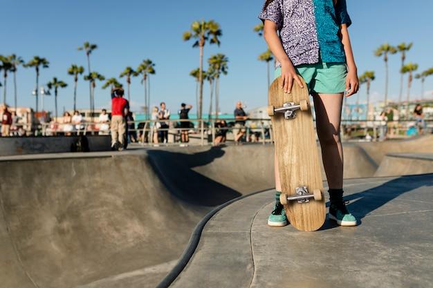 Jovencita con una patineta, en un skatepark en venice beach, la
