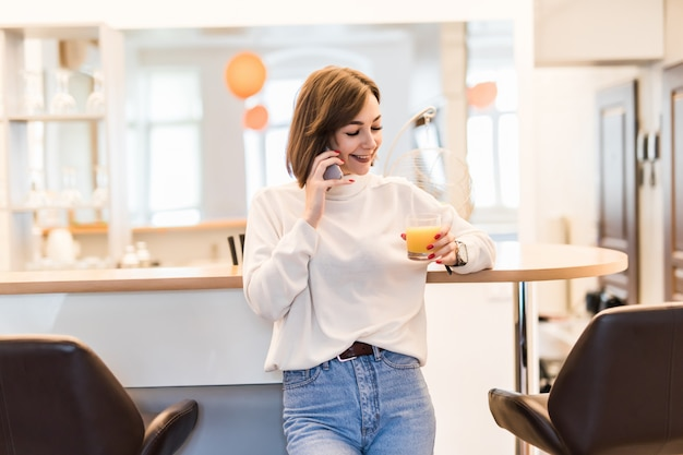 Jovencita está de pie cerca de la silla de bar en la cocina hablando por teléfono y sosteniendo un vaso con jugo de naranja