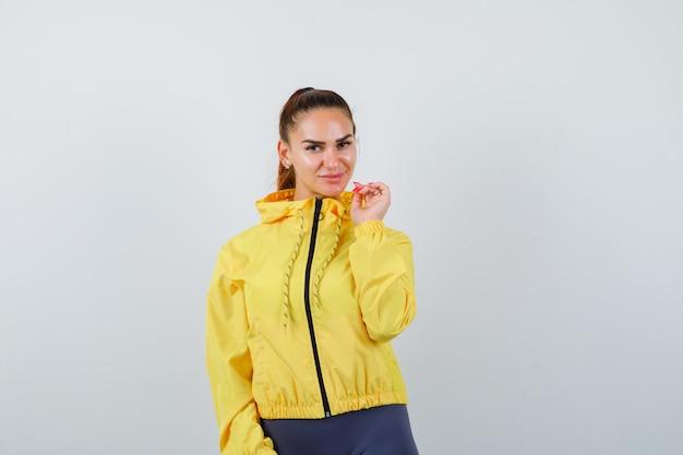 Jovencita posando en chaqueta amarilla y luciendo atractiva, vista frontal.
