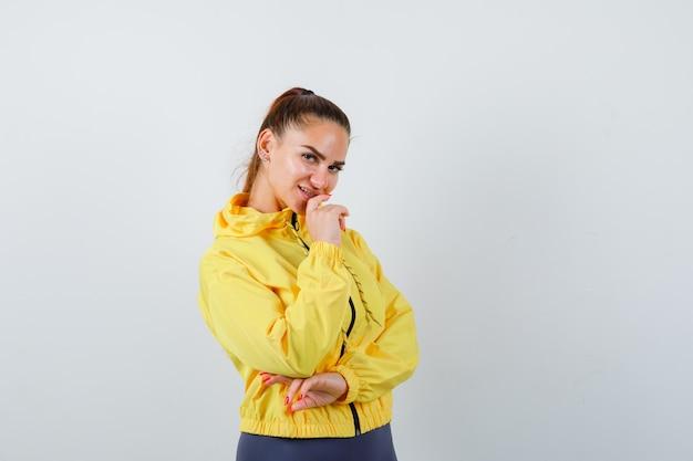 Jovencita posando en chaqueta amarilla y mirando alegre. vista frontal.