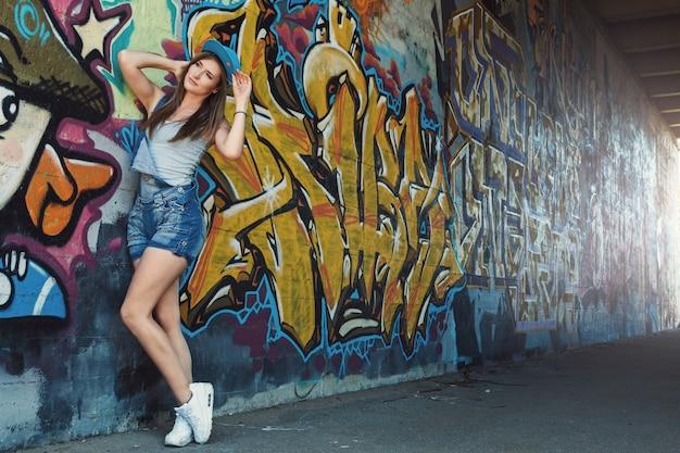Jovencita posando contra la pared con graffiti