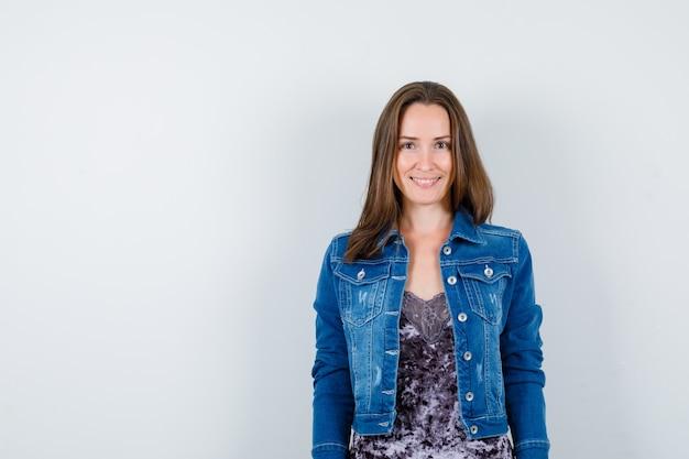 Jovencita posando mientras está de pie en blusa, chaqueta de mezclilla y mirando alegre. vista frontal. Foto gratis