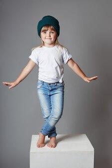 Jovencita posando sobre un fondo gris, brillantes emociones alegres en la cara de la niña