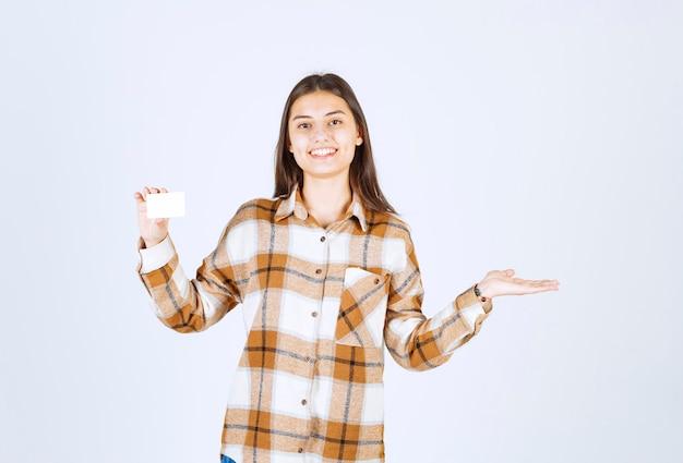 Jovencita posando con una taza de té en la pared blanca.