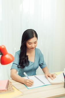 Jovencita preparándose para el examen de prueba con un portátil y libros escribiendo trabajos de curso de ensayo en el cuaderno estudiando en casa