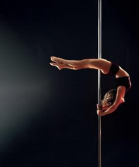 Una jovencita realiza elegantes trucos en el poste, volviendo la cabeza hacia el estudio de baile, izolirovannoi en una habitación oscura.