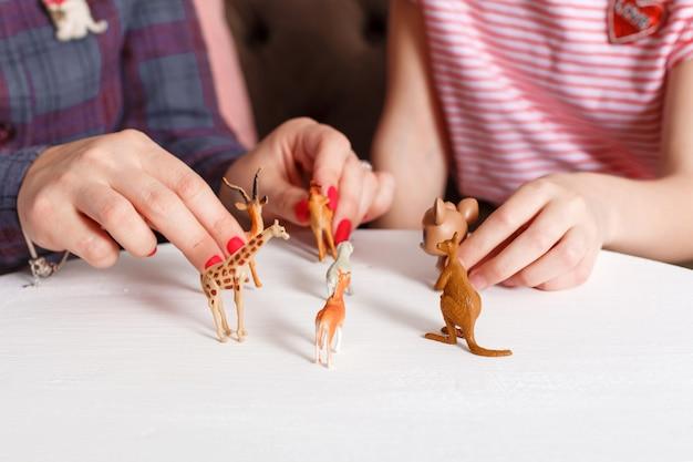 Jovencita en recepción en el psicoterapeuta. sesión de psicoterapia para niños. el psicólogo trabaja con el paciente. la niña juega animales de juguete junto con un médico terapeuta