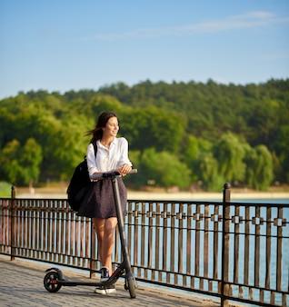 Jovencita de secundaria conduciendo su scooter eléctrico cerca del lago