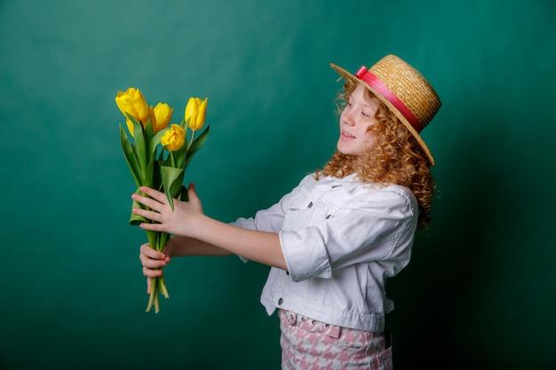 Jovencita sosteniendo un ramo de tulipanes amarillos