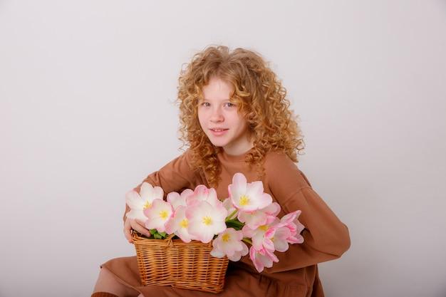 Jovencita sosteniendo un ramo de tulipanes rosados