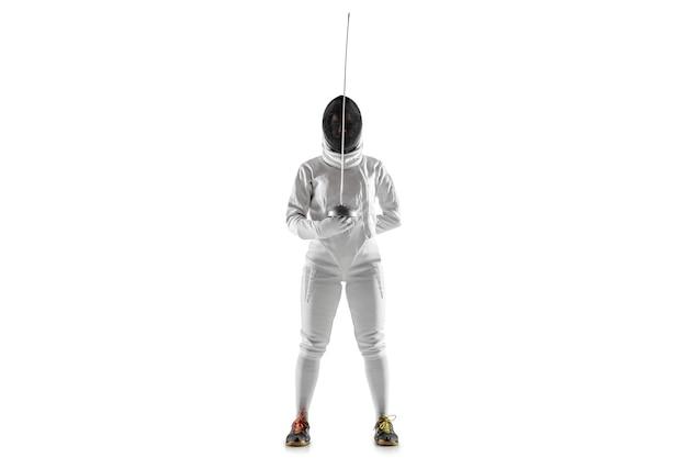 Jovencita en traje de esgrima con espada en mano aislado sobre fondo blanco.