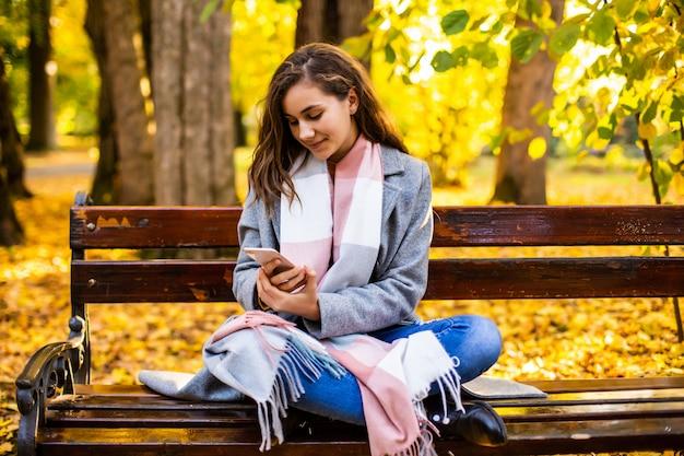 Jovencita usando un teléfono inteligente y mensajes de texto sentado en un banco de un parque urbano de otoño