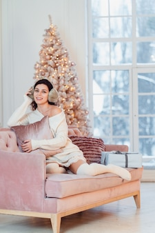 Jovencita vestida de blanco en el sofá en navidad