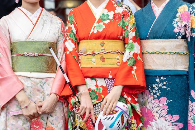 Jovencita vestida con un kimono japonés de pie frente al templo sensoji en tokio,