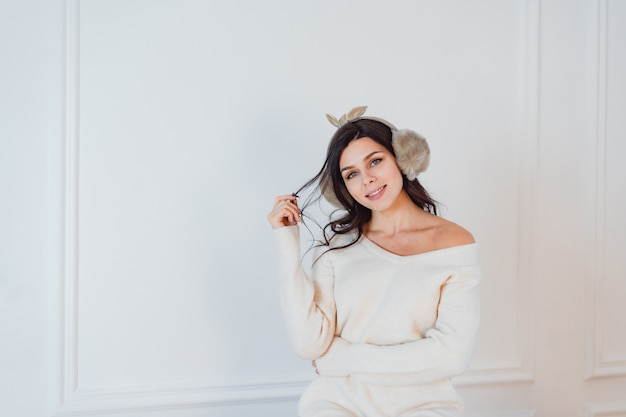 Jovencita con vestido blanco posando en la habitación