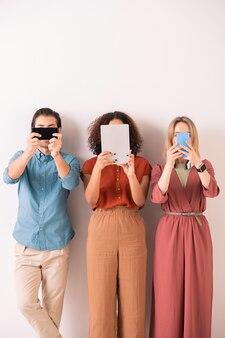 Jóvenes adictos multiétnicos con ropas brillantes de pie con dispositivos modernos que cubren sus rostros