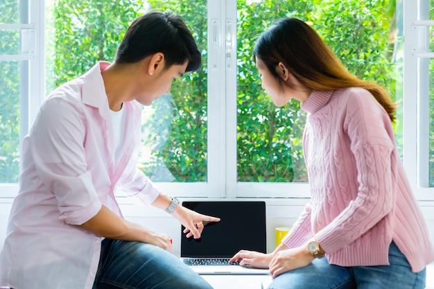Jóvenes adolescentes trabajando juntos con la computadora portátil