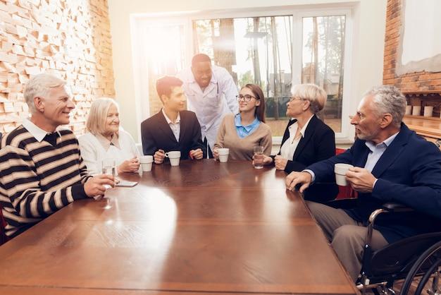 Jóvenes y adultos mayores se sientan juntos en la habitación del asilo de ancianos.
