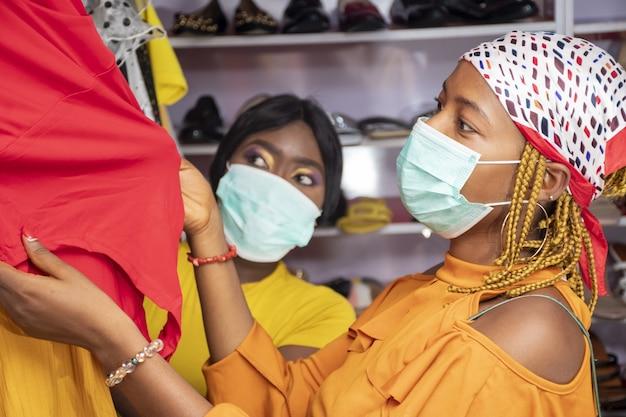 Jóvenes africanas de compras en una boutique de moda con máscaras médicas