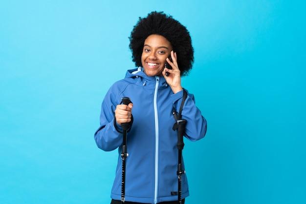 Jóvenes afroamericanos con mochila y bastones de trekking aislados sobre fondo azul manteniendo una conversación con el teléfono móvil con alguien