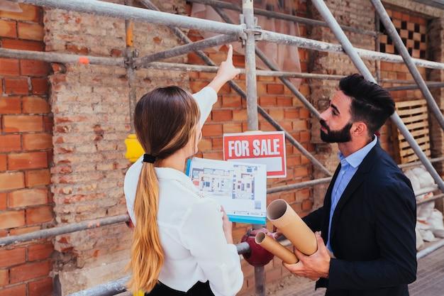 Jóvenes agentes inmobiliarios con andamio de fondo