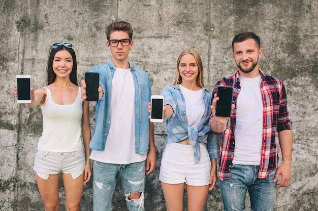 Jóvenes agradables y positivos mostrando sus teléfonos inteligentes