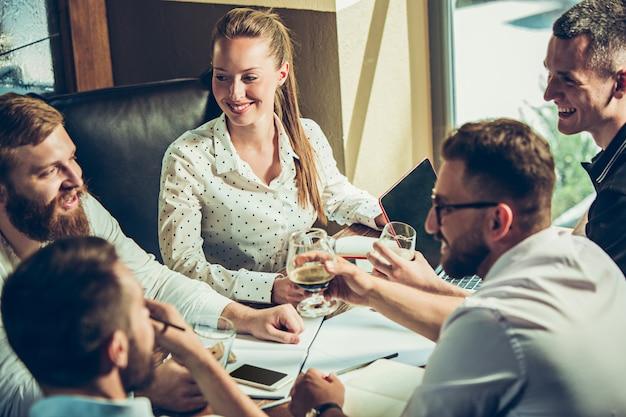 Los jóvenes alegres sonríen y hacen gestos mientras se relajan en el pub