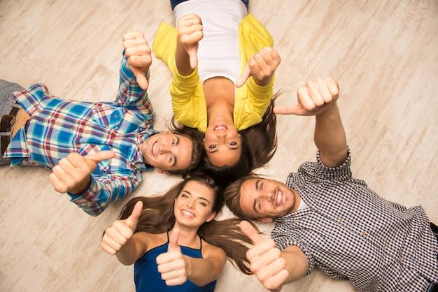 Jóvenes alegres tirados en el suelo mostrando los pulgares para arriba