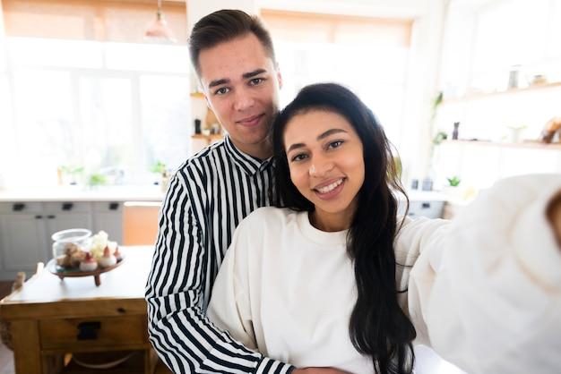 Jóvenes amantes abrazándose y tomando autofotos en la cocina.