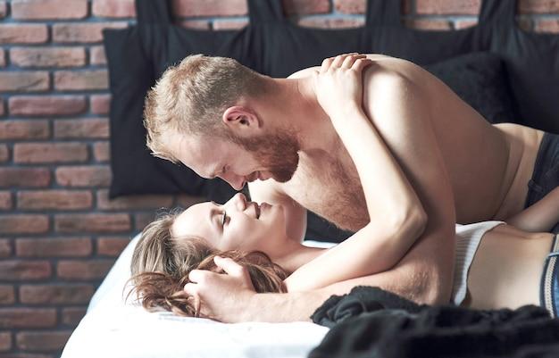 Los jóvenes amantes atractivos tienen parejas jugando juntas en la cama, vestidas con lencería sexy en una habitación de hotel.