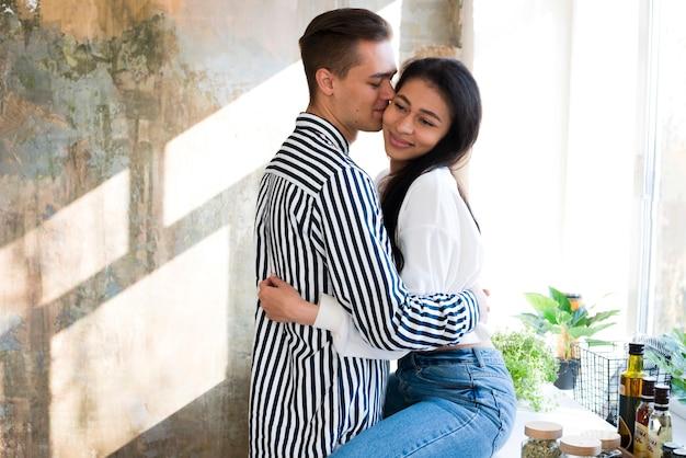 Jóvenes amantes felices abrazándose suavemente en la cocina
